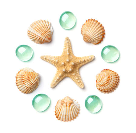Pattern in the form of a circle made of shells, starfish and green glass pebbles isolated on white background. Flat lay, top view. The concept of summer holidays and travel