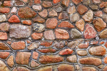 Wall of red granite cobblestones bonded with cement mortar