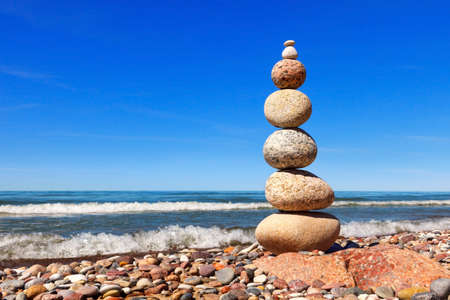 High Rock zen pyramid of white and pink pebbles on the beach. Concept of balance, harmony and meditation Stockfoto