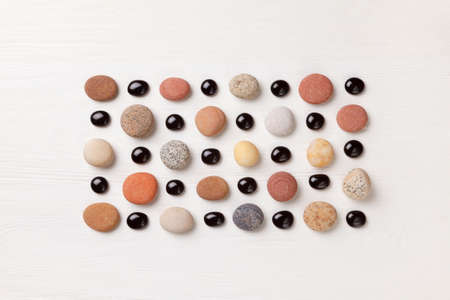 pattern of colored pebbles and black glass beads on white wooden background. Meditation and calmness concept. Flat lay, top view. copy space