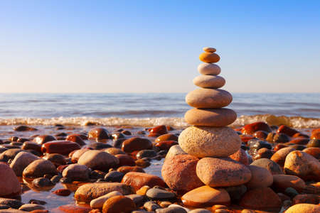 Rock zen pyramid of multi-colored pebbles in the pink rays of the setting sun against the sea. Concept of balance, harmony and meditation Stockfoto