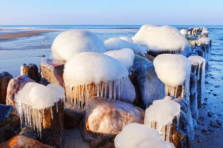 Icicles on an old breakwater on a sunny winter day Stockfoto