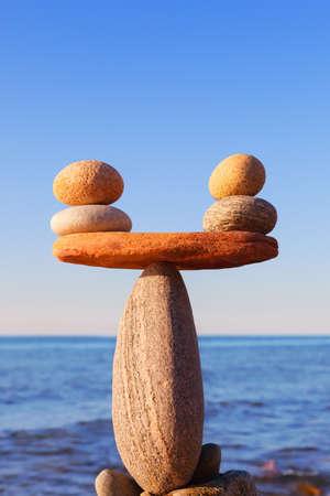 Symbolische Skala der Steine auf Seehintergrundnahaufnahme. Konzept von Harmonie und Gleichgewicht. Work-Life, emotionale Balance