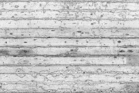 Gray, dirty, rough concrete wall with traces of wooden formwork