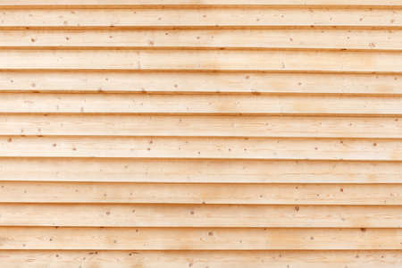 Large wall of light, yellow clean boards. Fragment of the facade of the building sheathed with boards in herringbone. Wood texture, background