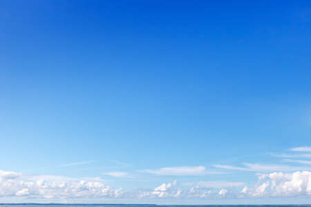 Clear blue sky and small white clouds on the horizon