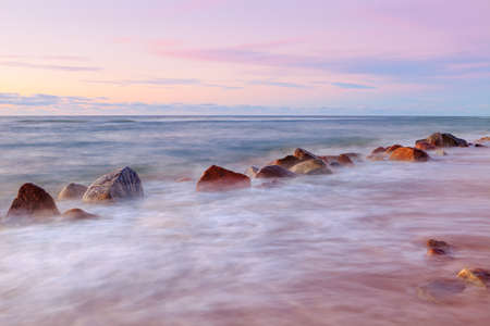 Sea sunset and big boulders sticking out from smooth wavy sea. long exposure