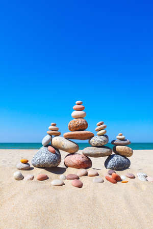Rock zen pyramid of colorful pebbles on a sandy beach on the background of the sea. Concept of balance, harmony and meditation