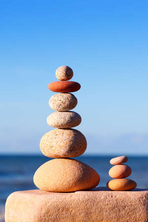 Rock zen pyramid of white and pink pebbles on the beach. Concept of balance, harmony and meditation