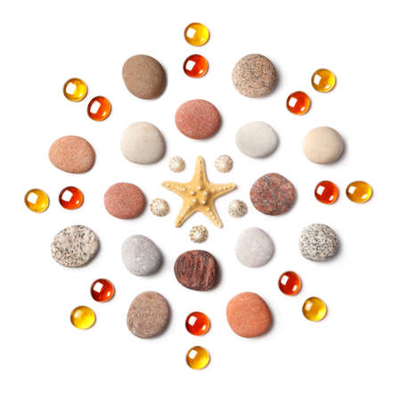 Pattern in the form of a circle of colored pebbles, starfish and orange glass beads isolated on white background. Meditation and calmness concept. Flat lay, top view Stockfoto