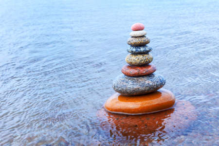 Rock Zen pyramid of colorful pebbles standing in the water. Concept of tranquility, balance, harmony and meditation. Soft focus, selective focus Stockfoto