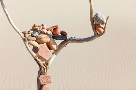 Balance of stones on a dry snag on a sand background. Concept of harmony, balance and meditation. Soft focus, selective focus, Copy space. Soft focus, selective focus Stockfoto