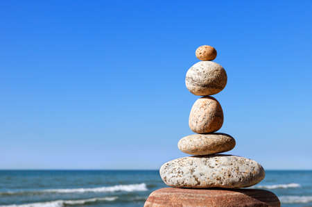 Rock zen pyramid of gray pebbles on a background of blue sky and sea.