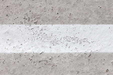 Grey concrete surface with wide white stripe in the middle. Background image, texture. copy space