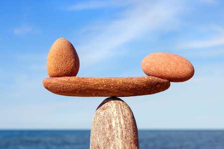 Symbolische Skala der Steine auf Seehintergrundnahaufnahme. Konzept von Harmonie und Gleichgewicht. Work-Life, emotionale Balance Standard-Bild