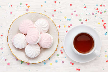 White and pink marshmallow (zephyr) and cup of tea on a wooden table. Top view Imagens