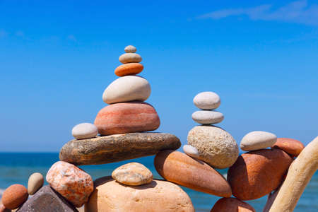Rock zen pyramid of colorful pebbles on a beach on the background of the sea. Concept of Life balance, harmony and meditation