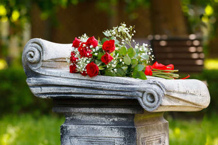bouquet of red roses on a gravestone in the cemetery