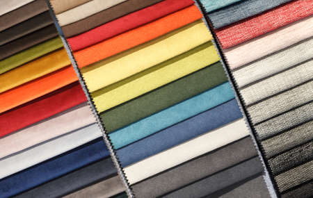 Multi-colored samples of upholstery fabric for sofas and chairs close-up. Selection of fabric for interior decoration