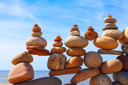 Lots of balanced, colorful stones on a beach on the background of the sea. Concept of Life balance, harmony and meditation