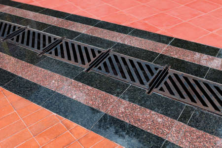 Pedestrian covering, lined with granite tiles with metal drainage grate. Sidewalk drainage system