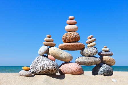 Rock Zen Pyramide der bunten Kieselsteine auf einem Sandstrand auf dem Hintergrund des Meeres. Konzept von Gleichgewicht, Harmonie und Meditation