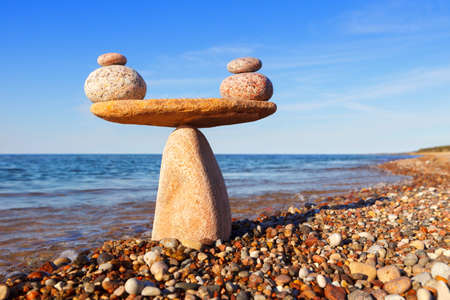 Symbolic scale of the stones on sea background. Concept of harmony and balance. work-life, emotional balance