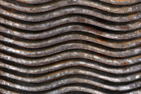 Old, rusty, wavy metal surface.