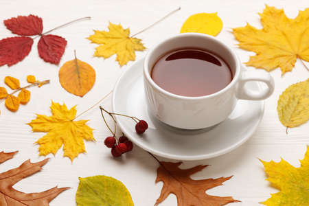 Yellow autumn leaves and a Cup of tea on a white wooden table. Autumn mood concept.