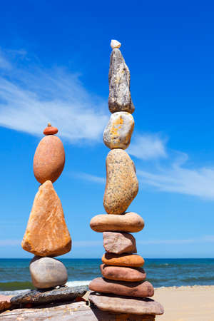 Two Rock zen pyramids of colorful pebbles on a beach on the background of the sea. Concept of balance, harmony and meditation