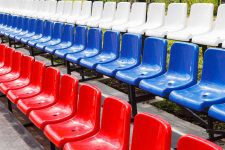 Plastic chairs red, blue and white in the stadium or Playground. Places for spectators of sports competitions