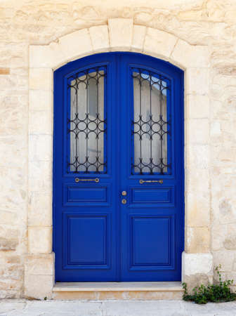 Beautiful old door in dark blue. Fragment of the facade of a Sandstone house, Cyprus, Europe Imagens