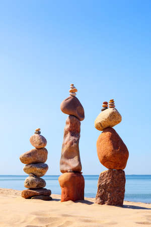 Three Rock zen pyramids of colorful pebbles standing on the beach, on the background of the sea. Concept of balance, harmony and meditation