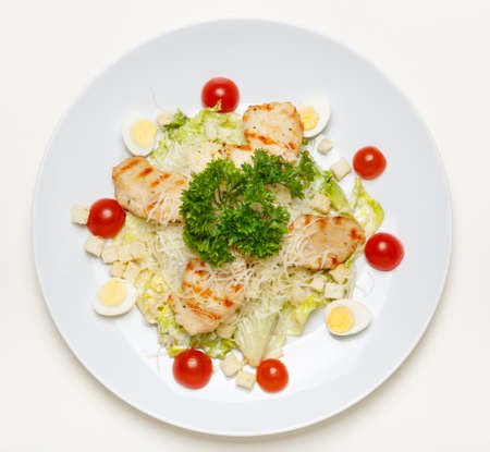 Caesar salad with chicken on a white plate and on a white background, top view