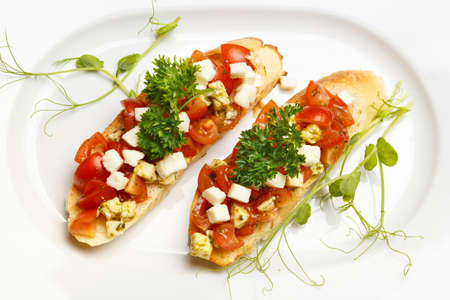 Bruschetta with mozzarella cheese and cherry tomatoes on a white plate decorated with young pea shoots