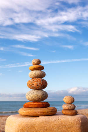 Rock zen pyramid of white and pink stones on the beach. Concept of balance, harmony and meditation