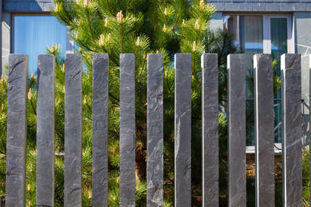 Modern fence made of bars (pillars) of gray, mountain, Silesian slate Imagens