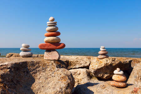 Rock zen pyramid of colorful pebbles on the background of the sea. Concept of balance, harmony and meditation