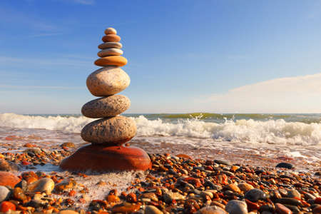 Rock zen pyramid of multi-colored pebbles in the pink rays of the setting sun against the sea. Concept of balance, harmony and meditation Imagens