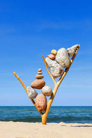 Multicolored balanced stones on an wooden snags, on a blue sky and sea background. Concept of harmony and balance. Imagens