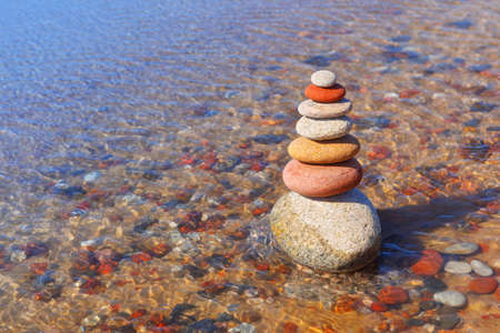 Rock zen pyramid of colorful pebbles standing in the water on the background of the sea. Concept of balance, harmony and meditation Imagens