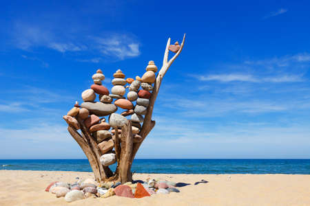 stack of multicolored balanced stones on an old wooden snags, on a blue sky and sea background. Concept of harmony and balance. Imagens