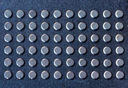 Tactile gray tiles on the sidewalk. Close up. Metal tactile indicators