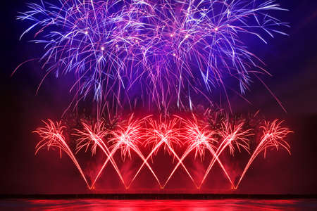 Beautiful, festive fireworks of red and blue color over the water with reflection