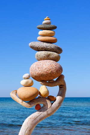 Multicolored balanced stones on an wooden snags, on a blue sky and sea background. Concept of harmony, balance and meditation Stock Photo