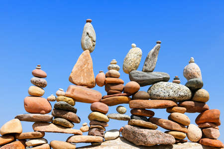 Lots of balanced, colorful stones against the blue sky. Concept of Life balance, harmony and meditation