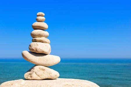 Rock-Zen-Pyramide aus weißen Steinen auf einem Hintergrund des blauen Himmels und des Meeres. Konzept von Gleichgewicht, Harmonie und Meditation