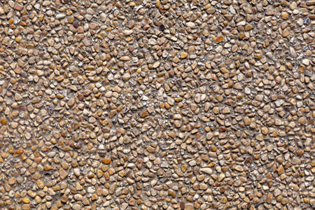 The wall is decorated with small natural pebbles of brown color. Background image, texture Stock Photo