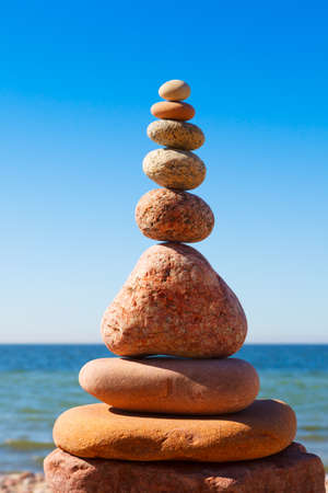 High Rock zen pyramid of white and pink pebbles on the beach. Concept of Life balance, harmony and meditation