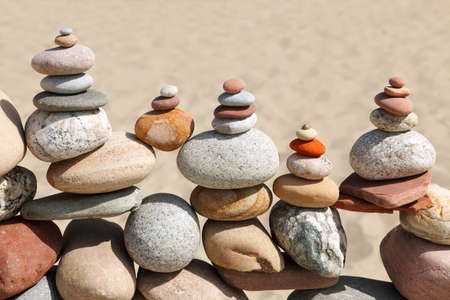 Lots of balanced, colorful pebbles on a beach on the background of the sand. Concept of Life balance, harmony and meditation